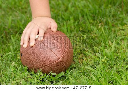Close up of child's hand on football with room for copy