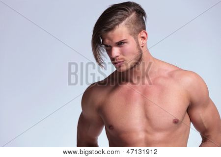 young topless man with greatly worked body looking away from the camera. on gray background