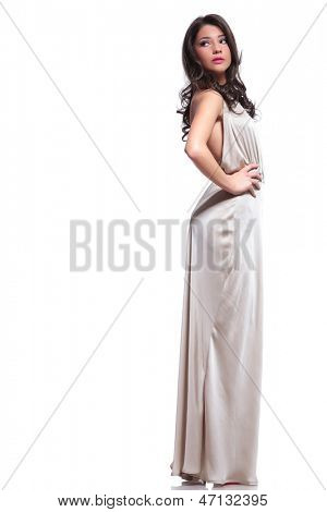 full length photo of a young beauty woman looking back, over her shoulder with her hands on her hips. isolated on white background