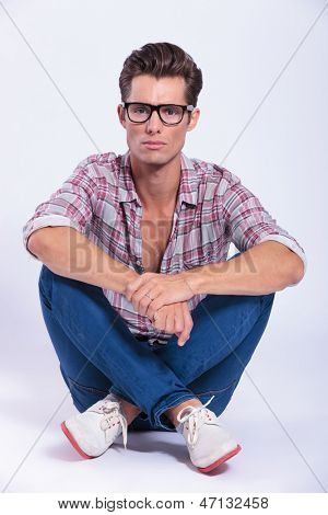 casual young man sitting on the floor with legs crossed and looking at the camera with a serious expression. on gray background