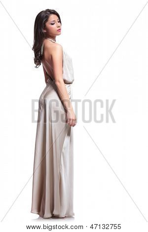 full length photo of a young beauty woman standing with her back at the camera and looking down. isolated on white background