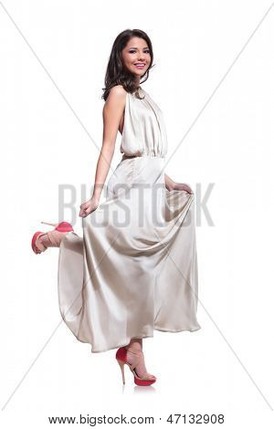 full length photo of a young beauty woman standing on one leg and smiling for the camera. isolated on white background