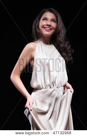 young beauty woman holding her dress with both hands and looking up with a smile on her face. on black background
