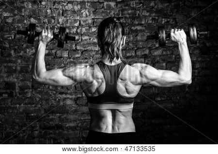 strong woman is training with barbells