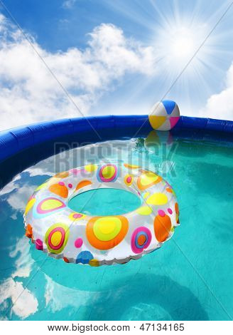 Inflatable pool with floating plastic toys.