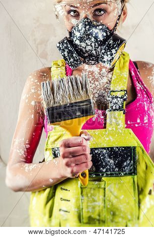 Female Construction Worker Wearing Respirator Holding Paint Brush