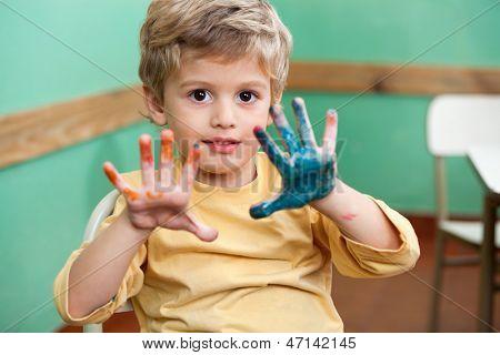 Portrait of little boy showing colored palms in art class