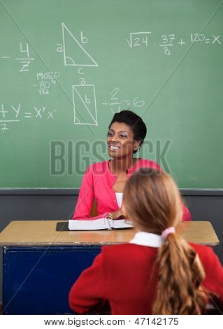 Young African American female teacher looking away with female student in foreground at classroom