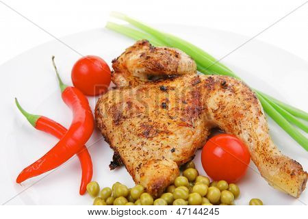 barbecued meat : chicken ham garnished with green onion pens and red chili hot pepper on white plate isolated over white background