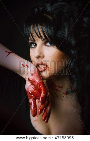 Beauty Vampir Girl mit Blut auf Gesicht auf schwarzem Hintergrund