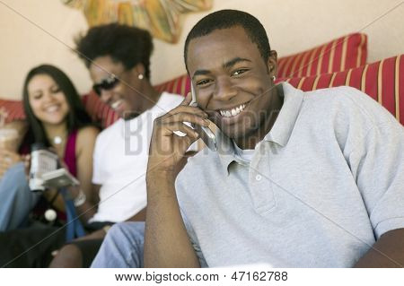 Portrait of a happy man using cellphone and blurred friends with camcorder in the background at home