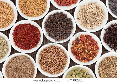 Spice and herb selection in white porcelain bowls over bamboo background.