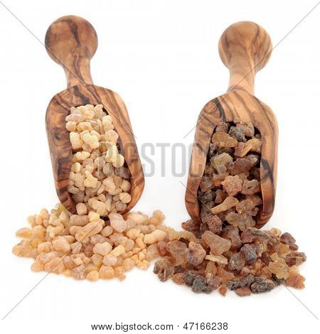 Frankincense and myrrh in olive wood scoops over white background.