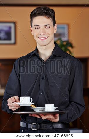Smiling waiter bringing hot cup of coffee in a caf���©