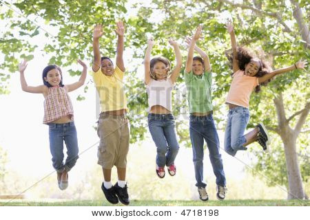Five Young Friends Jumping Outdoors Smiling