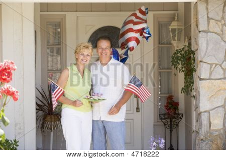 Couple At Front Door On Fourth Of July With Flags And Cookies Smiling