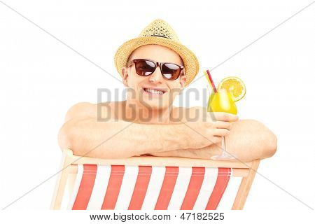 Smiling shirtless guy with cocktail posing on a beach chair isolated on white background