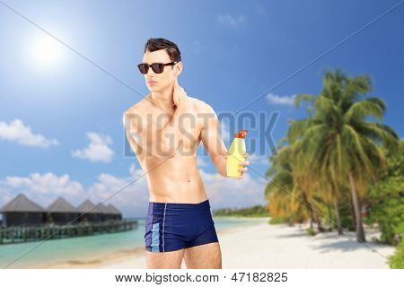 Handsome guy putting on sun cream, on a sandy beach with palm trees and water villa cottages at Kuredu island, Maldives, Lhaviyani atoll