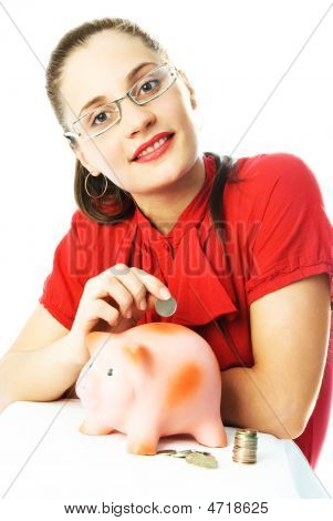Happy Woman Putting A Coin Into The Piggy Bank
