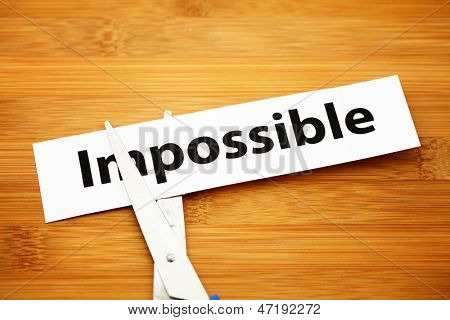 Word impossible cut to possible over wood background
