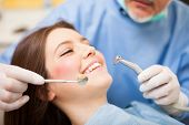 stock photo of hand drill  - Dentist doing a dental treatment on a female patient - JPG