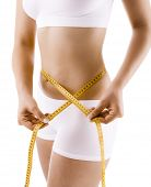 stock photo of flat stomach  - Woman measuring her waist body isolated on white background - JPG
