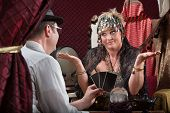 stock photo of gullible  - Customer showing happy tarot cards to fortune teller - JPG