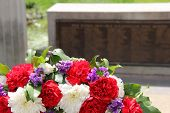 stock photo of carnations  - Colorful remembrance wreath made with carnations and greenery at war memorial - JPG