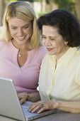 Mother and Daughter Using Laptop on Patio