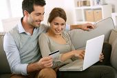 image of couch  - Couple using credit card to shop on internet - JPG