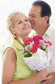 picture of portrait middle-aged man  - Husband and wife holding flowers husband kissing wife on the cheek and smiling - JPG
