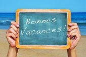 stock photo of bonnes  - someone holding a blackboard on the beach with the sentence bonnes vacances - JPG