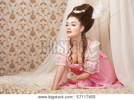 Old fashioned sexy woman in pink dress lying on bed