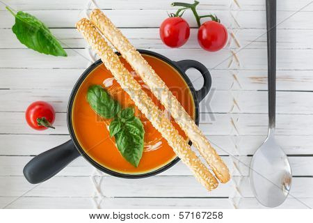 Overhead View Of A Tomato Soup In A Black Casserole, Drizzled With Cream, And Garnish With Leaves Of