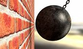 picture of ball chain  - A regular metal wrecking ball attached to a chain hitting and breaking a face brick - JPG