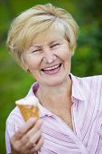 Contentment. Jubilant Ecstatic Old Woman Holding Ice-cream And Laughing