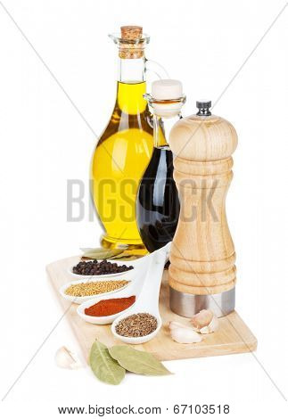 Colorful herbs and spices selection. Seasoning and aromatic ingredients on cutting board. Isolated on white background