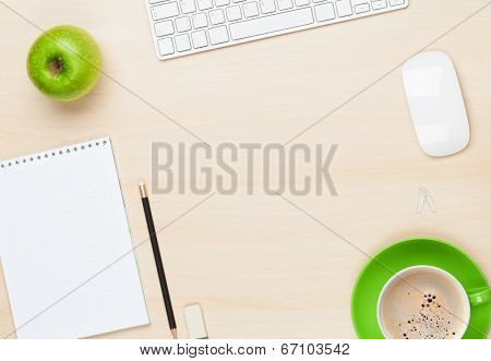 Office table with notepad, computer and coffee cup. View from above