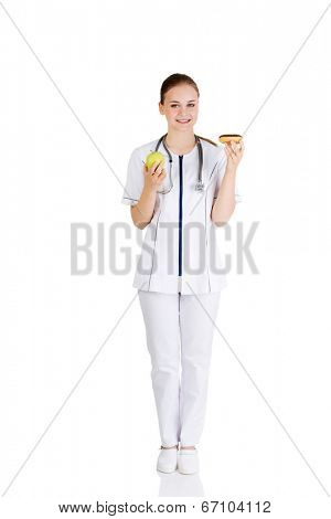 Dietician holding sweet doughnut and fresh healthy green apple. Isolated on white