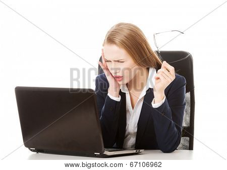 Surprised and curious business woman cannot believe what she sees in the laptop screen. Isolated on white.