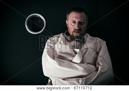 Insane Man In A Cell Wearing A Straitjacket