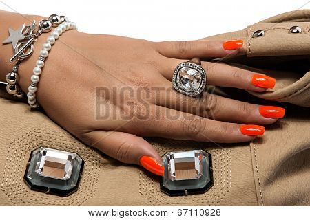 closeup of the woman's hand wearing luxury ring, orange nail art manicure with mirror leather bag. wearing large silver ring, isolated on white studio background