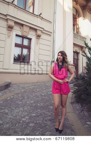 Fashion, Glamorous And Attractive Woman Dressed In A Sexy Sleeveless Pink Jumpsuit Posing In Full Bo