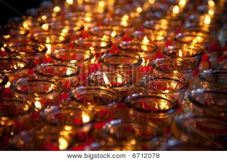 red prayer candles lit at a temple