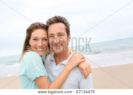Happy 40-year-old couple enjoying day at the beach