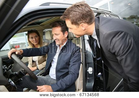 Car dealer showing vehicle  to clients