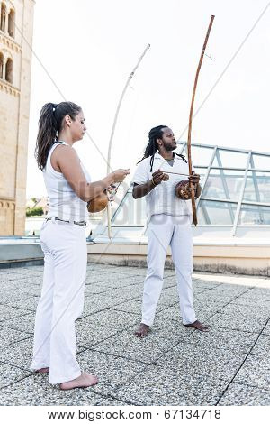 Young pair partners capoeira berimbau musical instrument in their hands