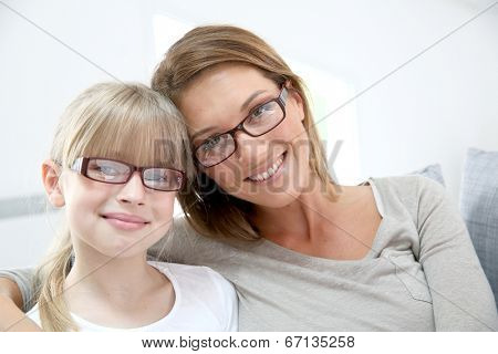 Portrait of smiling woman and girl wearing eyeglasses