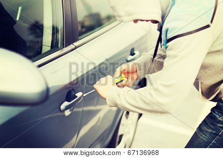 transportation, crime and ownership concept - thief breaking the car lock
