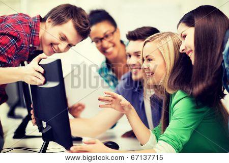 education concept - students looking at computer monitor at school